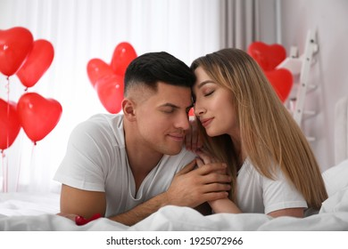 Lovely couple on bed in room decorated with heart shaped balloons. Valentine's day celebration