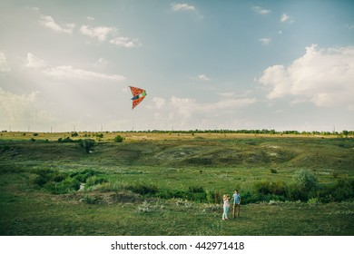 lovely couple play air kite at green picturesque meadow at countryside