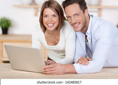Lovely couple playing through laptop on the floor