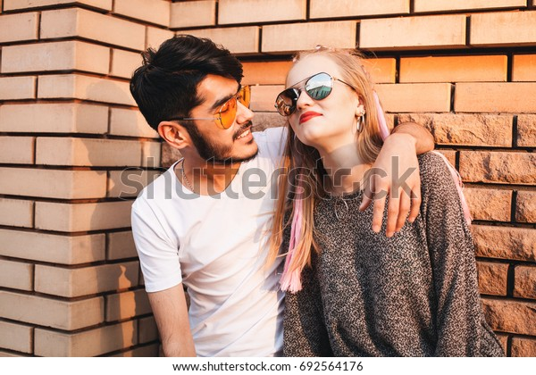 Lovely couple is posing near the wall in city.