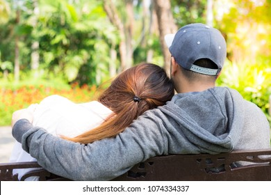 Lovely couple sit in park. Charming beautiful girlfriend lay her head on her boyfriend's shoulder, boyfriend hug her that look so romantic. Lovely lover is in love each other. They're warm hearted