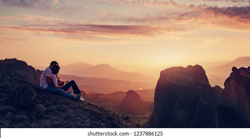 Lovely Couple sitting on rock in the evening, beautiful dusk. Wonderful Panoramic view of the rocks and monasteries of Meteora, Greece. Mysterious colorful sky, during sunset. Awesome Nature Landscape