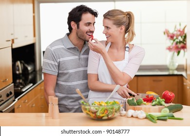Lovely couple slicing pepper in their kitchen