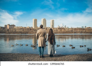Lovely couple is staying near a river and holding hands