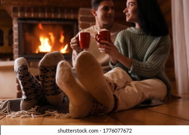 Lovely couple with sweet cocoa near fireplace indoors, focus on legs