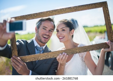 a lovely couple is taking funny selfies for their wedding, taking a frame in front of their faces, behind them a lovely country road