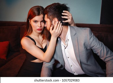 lovely couple in tender passion. young casual fashion models posing in home. brutal bearded man with mustache in grey jacket with pretty girl with dark hair and big lips with red lipstick in dress