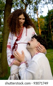 Lovely couple in Ukrainian national costumes outdoors. The woman is pregnant. Father hugging her tummy.