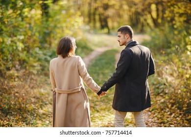 lovely couple walking around the park during autumn