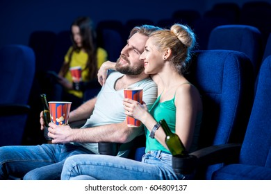Lovely couple watching film sitting together with popcorn in the cinema