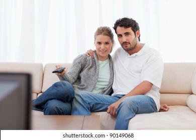Lovely couple watching TV in their living room