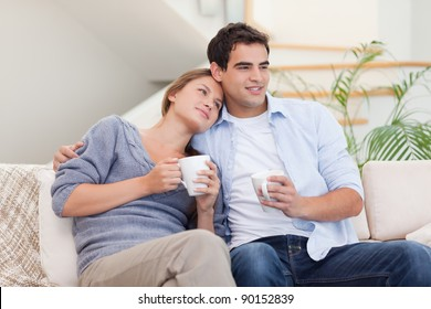 Lovely couple watching TV while drinking tea in their living room