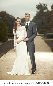 Lovely couple in wedding style dress posing in park