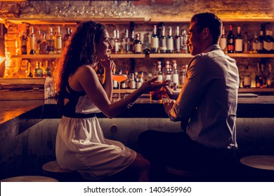 Lovely couple. Young lovely couple feeling relaxed while sitting at the bar stand and talking