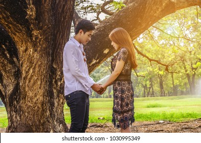 The lovely couples stand together Under the big tree on summer day