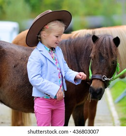 Lovely cowgirl caressing little pony horse in the farm. Pretty preschooler girl wearing cowboy hat playing with animals outdoors on sunny day.