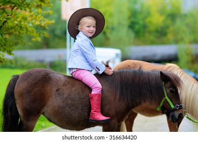 Lovely cowgirl riding little pony horse in the farm. Pretty preschooler girl wearing cowboy hat playing with animals outdoors on sunny day.