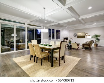 Lovely craftsman style dining and living room interior with coffered cealing and paneled walls. Floor to ceiling glass doors lead out to stunning covered patio area . Northwest, USA