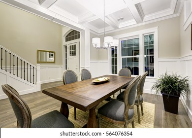 Lovely craftsman style dining room with coffered cealing over wooden dining table surrounded by grey chairs atop sisal rug. Northwest, USA