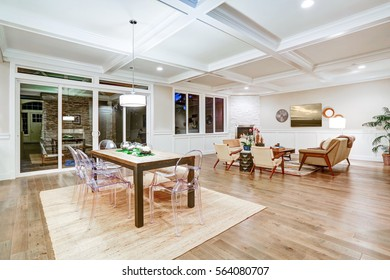 Lovely craftsman style dining space with coffered cealing over rustic wooden dining table surrounded by modern glass chairs. Floor to ceiling glass doors lead out to stunning patio. Northwest, USA