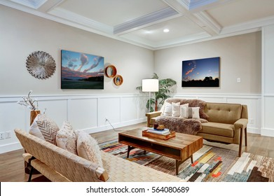 Lovely craftsman style living room with coffered cealing over light beige walls with board and batten wood paneling. Comfortable sofa adorned with pillows and taupe shag throw blanket. Northwest, USA