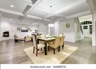 Lovely craftsman style open plan interior of dining and living room with coffered cealing , paneled walls and gray hardwood flooring. Northwest, USA
