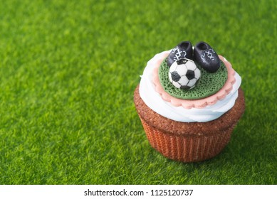 Lovely Cupcake in a football style on a green lawn - top view