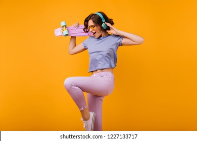 Lovely curly girl in pink pants jumping on orange background while listening music. Indoor photo of glad caucasian lady in headphones dancing with skateboard.