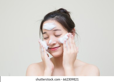 lovely cute Asian girl enjoy with her skincare product that she apply on her face to make healthy young skin