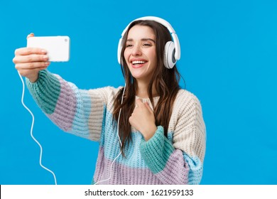 Lovely and cute girlfriend contact boyfriend via internet, online video-calling, holding smartphone extended arm, wearing winter sweater, big headphones, taking selfie and smiling, blue background