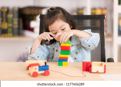 Lovely cute little Asian girl in jeans shirt concentrate  playing wood block toys on desk. Concept for funny activity of young kids in free time.