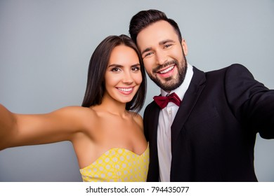 Lovely, cute, smiling, attractive, sexy couple, husband and wife in elegant outfit, tux, dress with beaming smiles making selfie together in two hands over grey background, 14 february