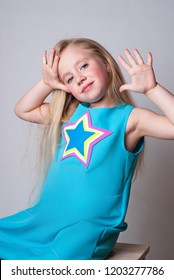 Lovely dancer sitting on a wooden chair in a blue clothes with a star on it waiving hands and looking happy
