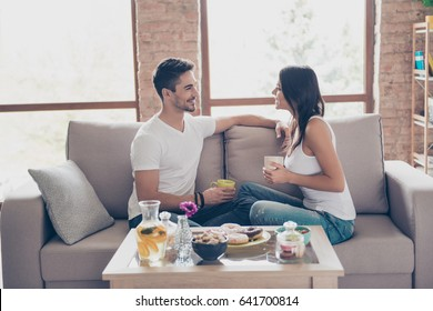 Lovely date. Beautiful couple in casual outfit is sitting on sofa indoors and smiling. They are drinking mugs of tea and look at each other and talk