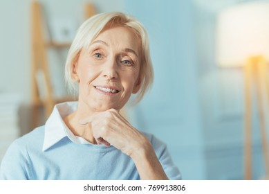 Lovely day. Cheerful aged woman feeling happy while sitting at home with her fingers touching the chin and smiling kindly