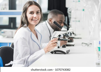 Lovely day in the laboratory. Top view of smiling young female scientist using microscope and looking at camera while working in the laboratory