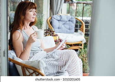 Lovely dreaming middle-aged redhead woman relaxing on balcony with plaid and cup of tea.