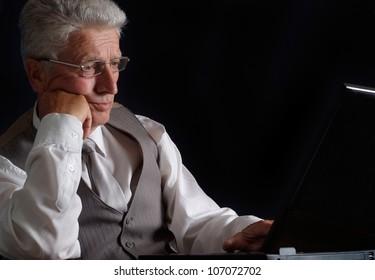 Lovely elderly man in suit on black background