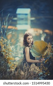 Lovely elf girl in a green dress in the forest with a huge leaf of burdock, a summer fairy tale