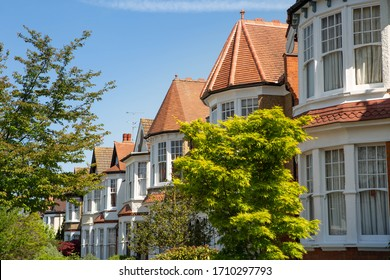 Lovely English Edwardian residential houses in a row with spectacular wooden bay casement windows. Front view on the properties from the street with green trees on a sunny day. London, UK 21/04/2020