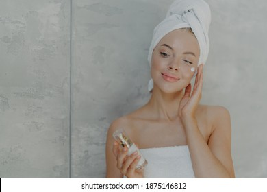 Lovely European woman applies facial moisturizer holds bottle of body lotion, has healthy skin, well groomed complexion wears wrapped towel on head after taking shower, poses against grey background