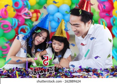 Lovely family celebrating birthday party and cutting a birthday cake together with colorful balloons background