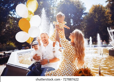Lovely family dressed in the same clothes sits on the fountain with their children and yellow balloons
