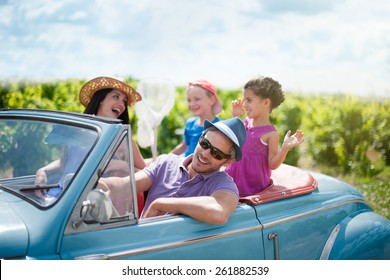 A lovely family is going on vacation in a convertible retro car. they drive on a country road on a sunny day