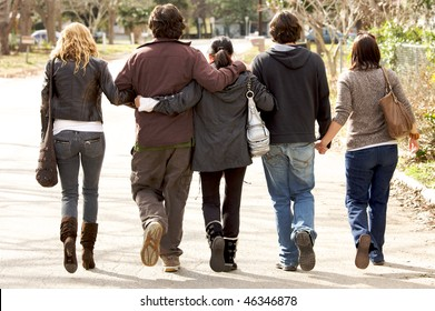 A lovely  family holding eachother walking away from camera