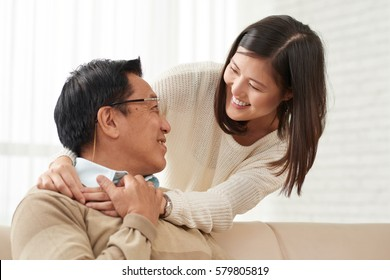 Lovely family moments: Asian young woman standing behind her senior dad and hugging him tenderly, he turned to her and smiling