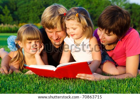 Lovely family reading a book on the  grass