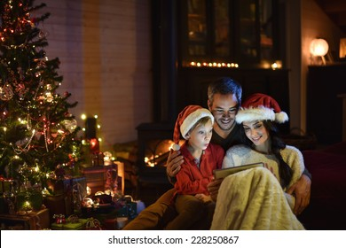 lovely family sharing digital tablet near the wood stove on a winter evening, enjoying the warm Christmas atmosphere in their living room, mother and child wearing a hat of Santa Claus