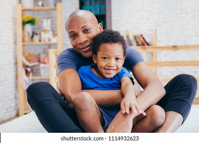 Lovely father and smiling son hugging and playing together in indoor home