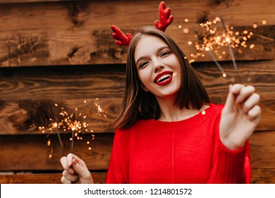 Lovely female model with straight hairstyle holding bengal lights with inspired smile. Cute woman in red sweater preapring for new year.